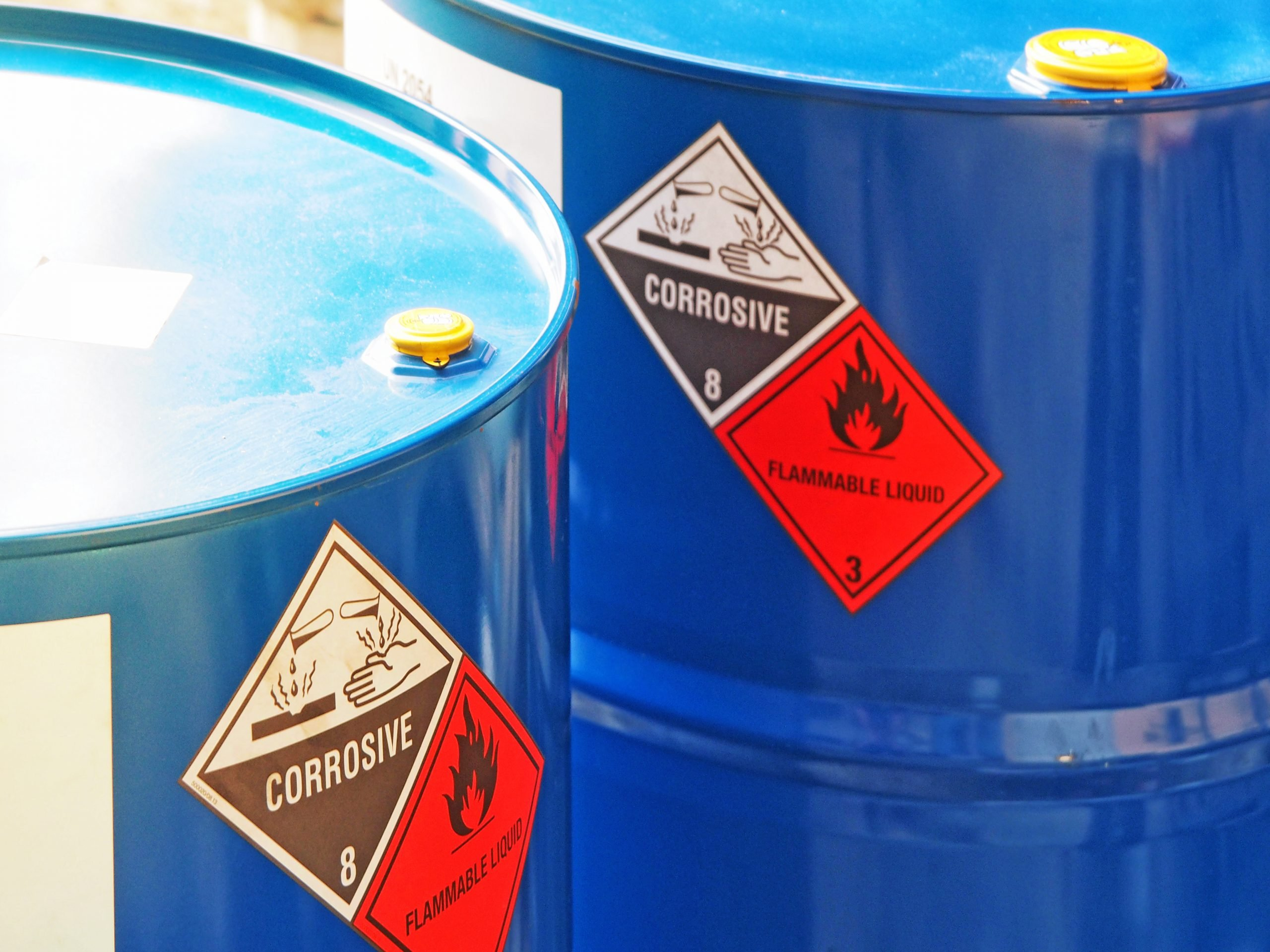 hazardous dangerous chemical barrels ,have warning labels of corrosive & flammable liquid