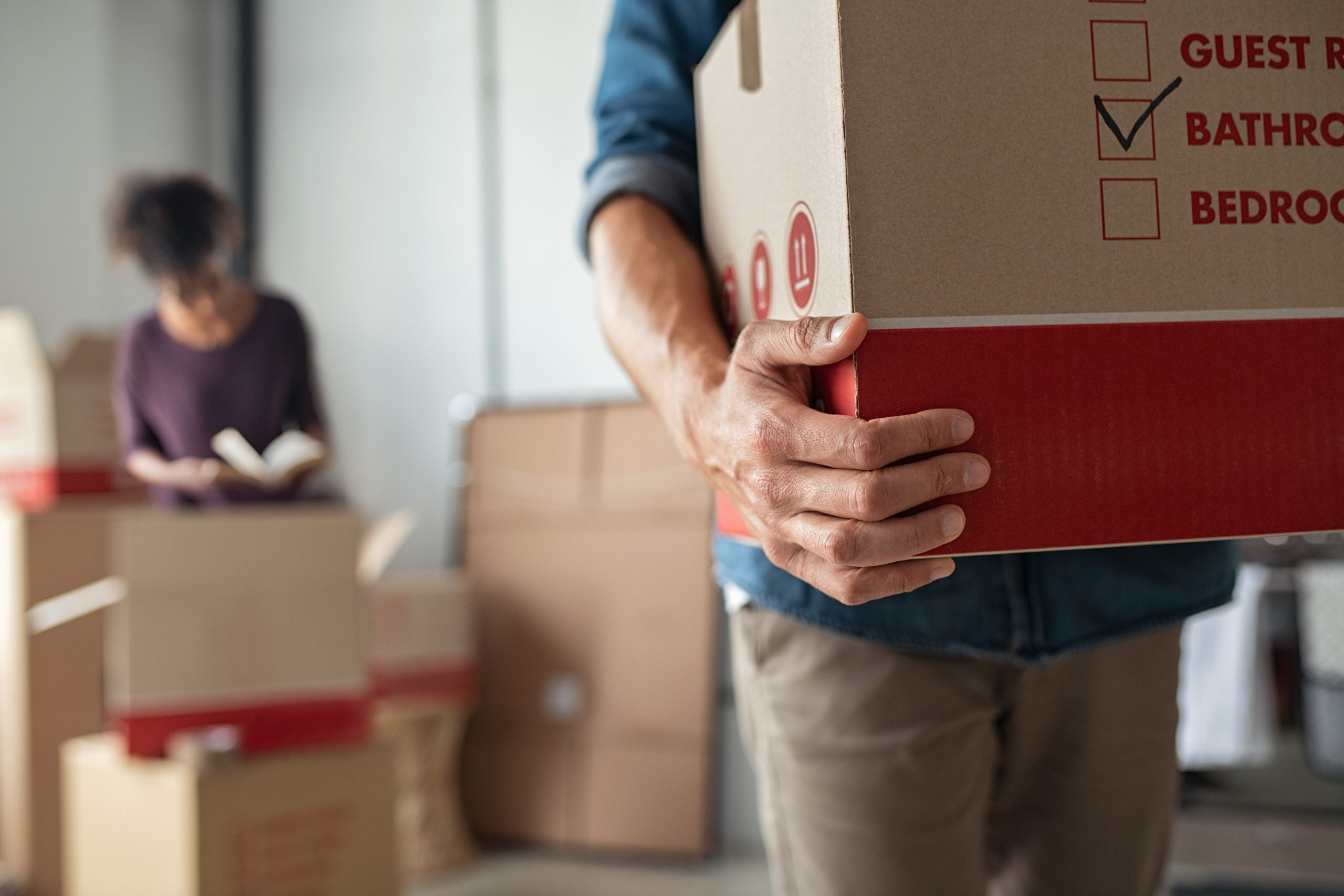 Hands holding cardboard box during relocation