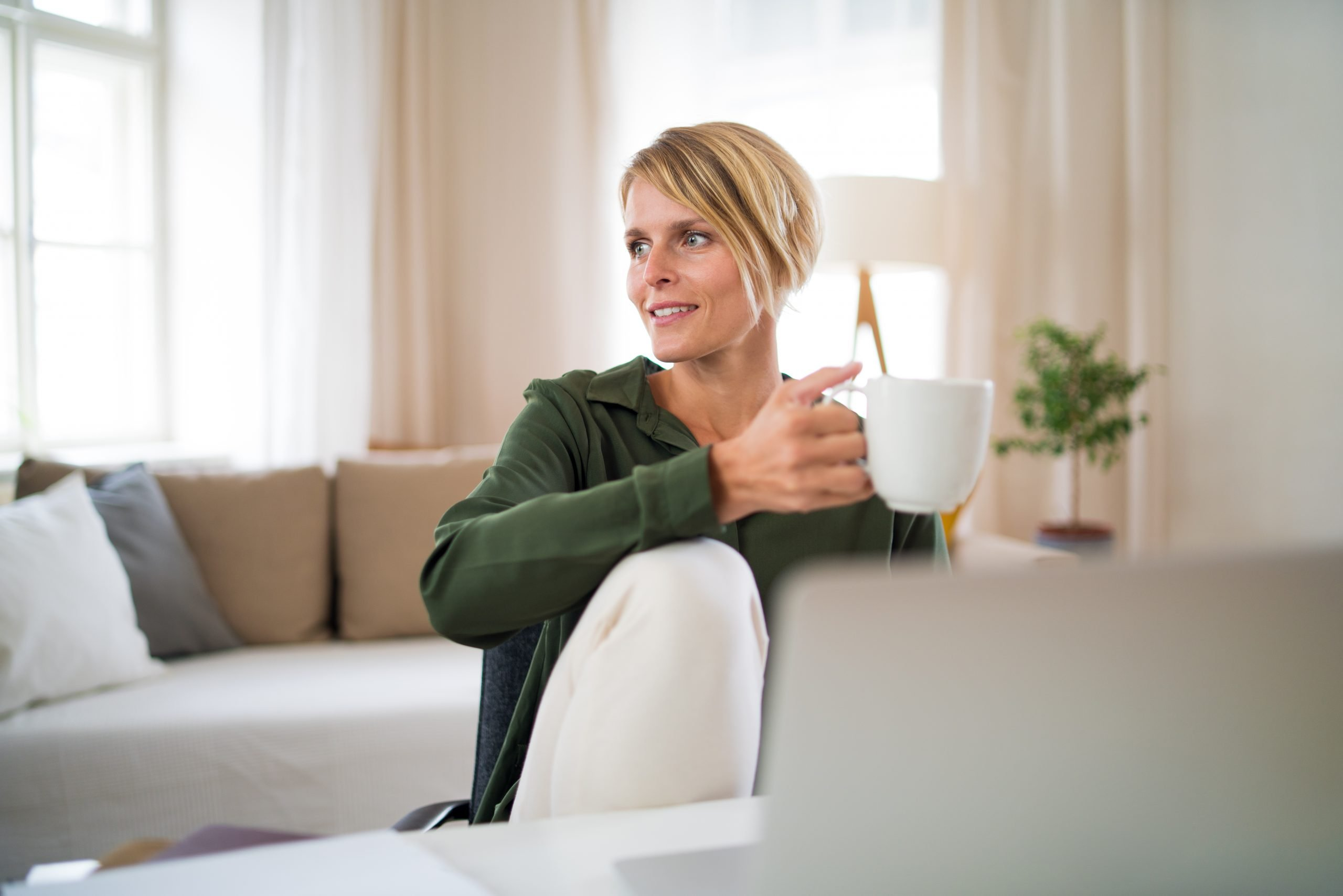 Portrait of business woman indoors in office sitting at desk, holding cup of tea.