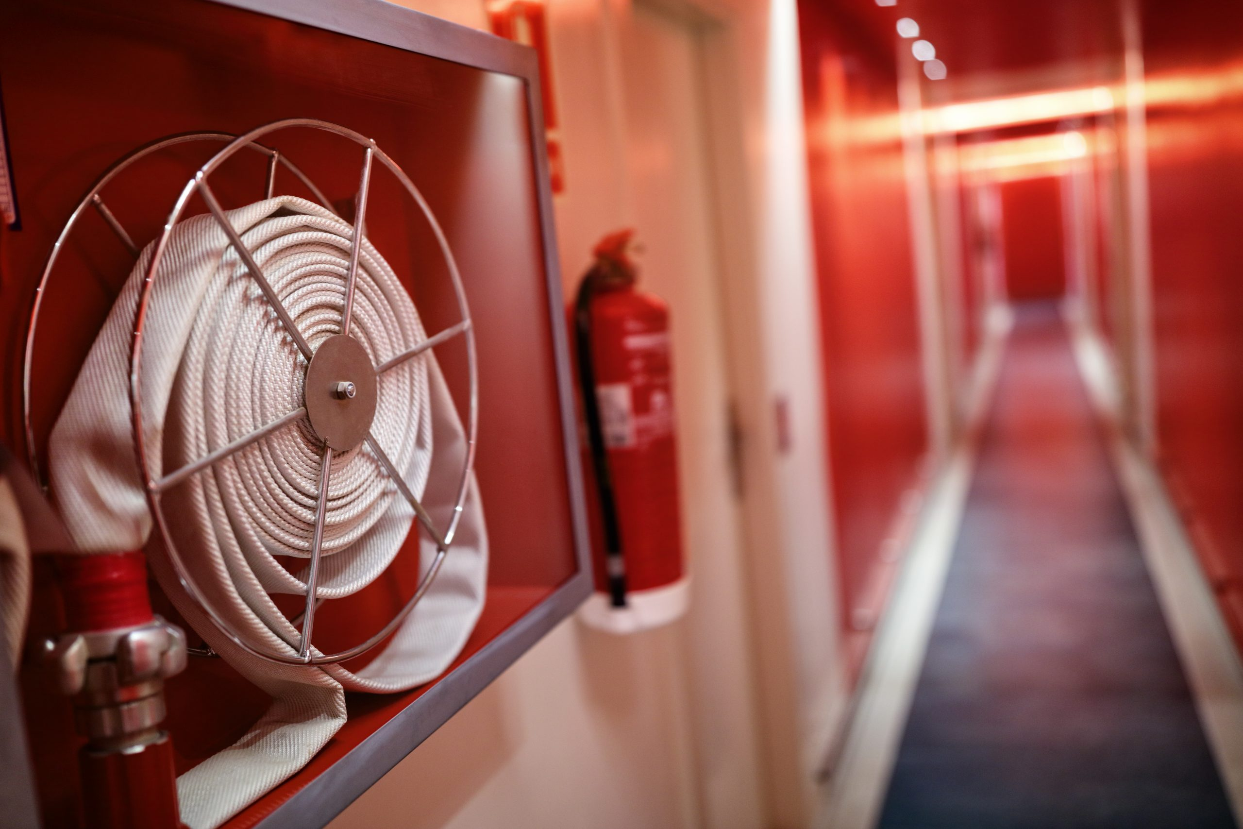 Fire extinguisher and hose reel in hotel corridor