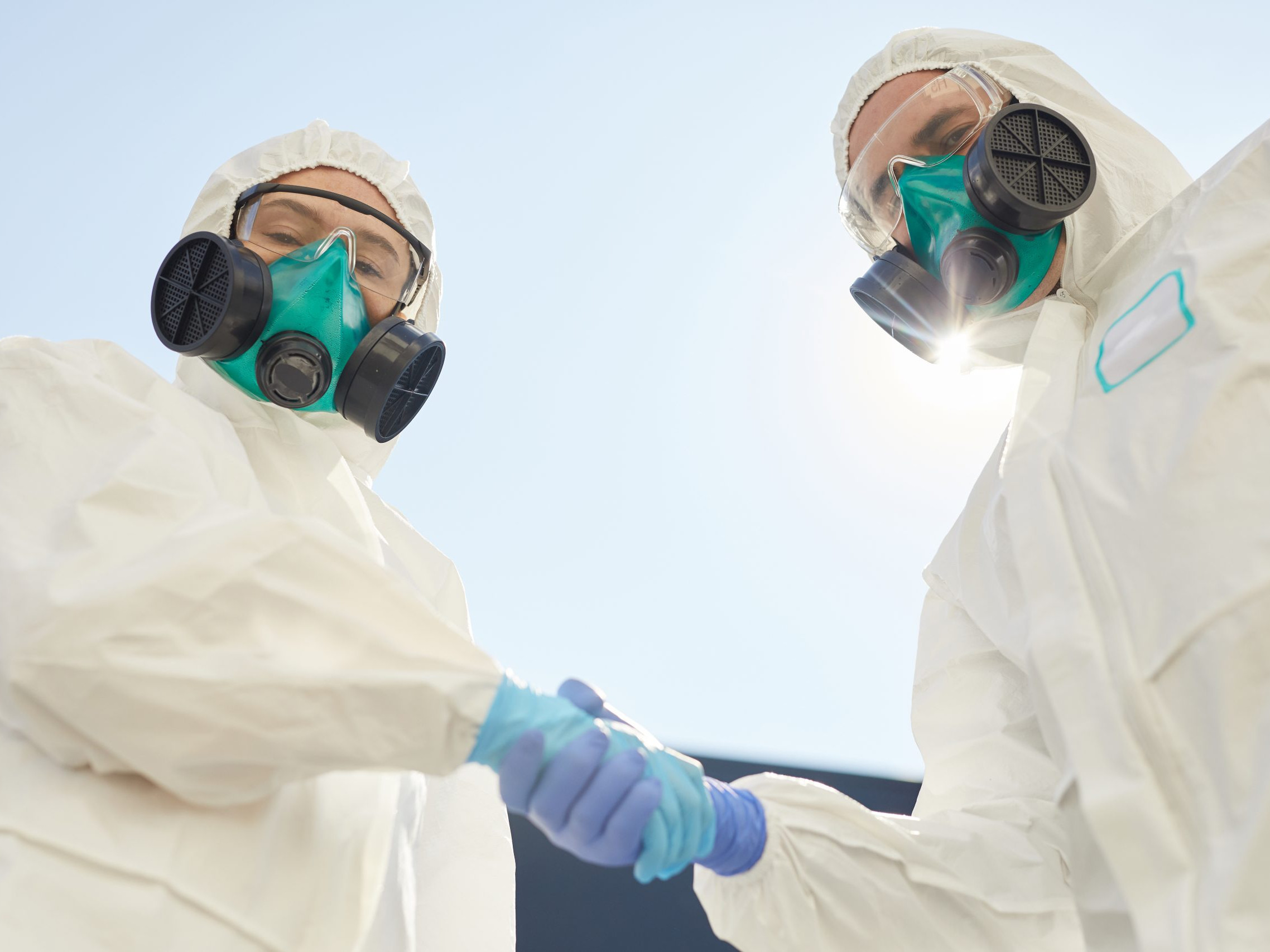 Two Disinfection Workers Shaking Hands